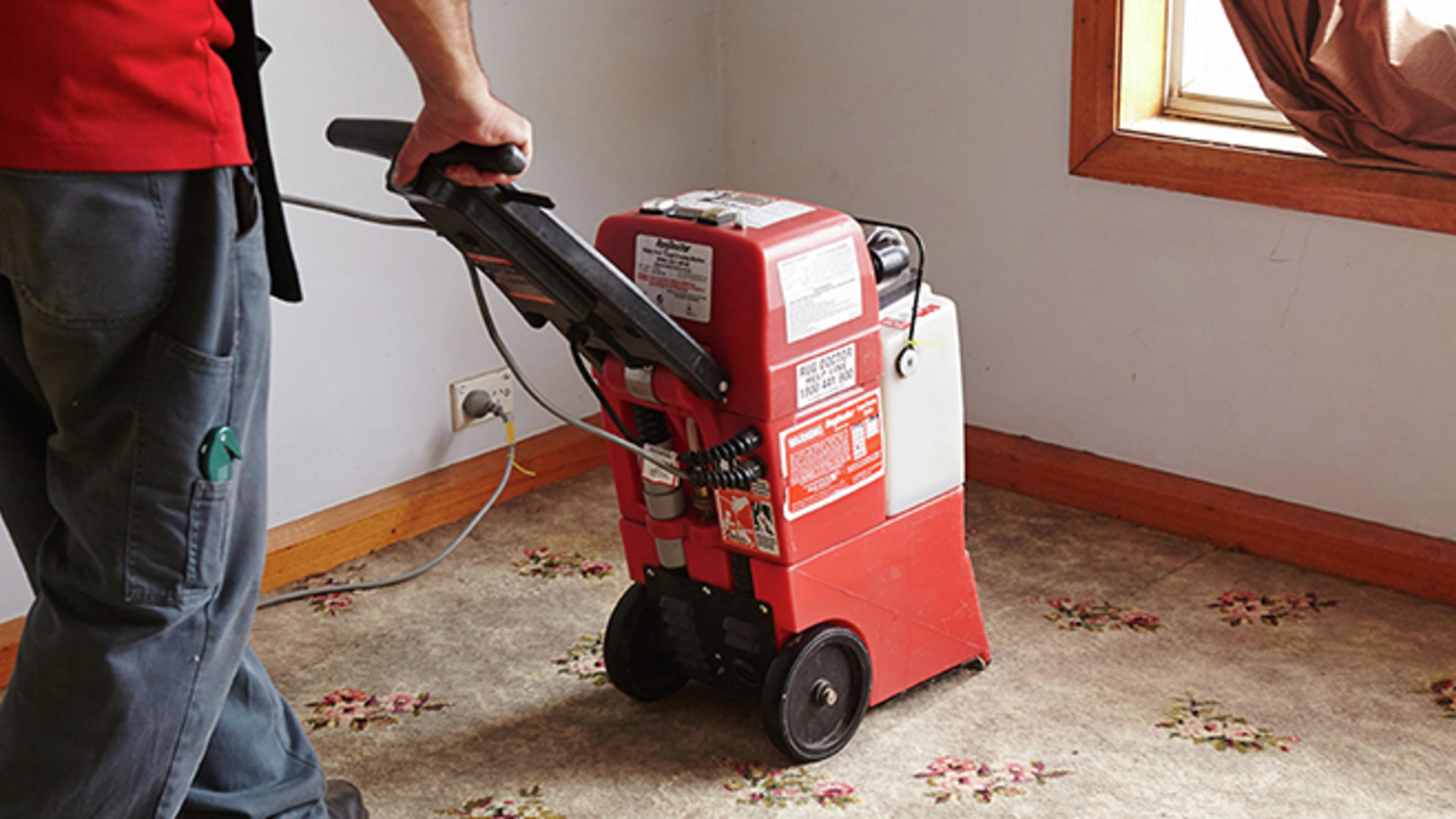 Person using a carpet cleaner on a carpeted floor
