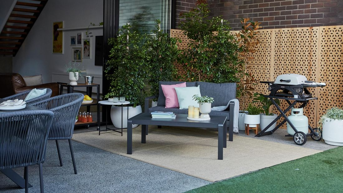 Outdoor setting in courtyard next to BBQ and plants