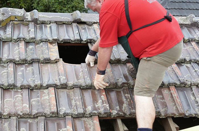 Tiles being removed from a roof to make way for a new skylight