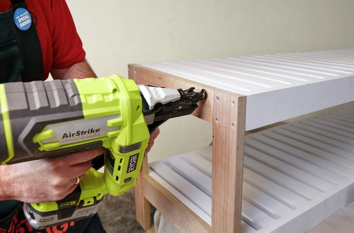 Person nailing shelves to frame