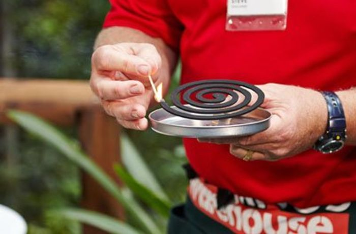 A Bunnings team member lighting a mosquito coil
