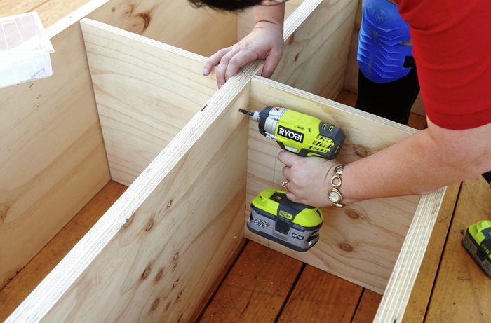 A hole being drilled into a laundry basket dresser frame