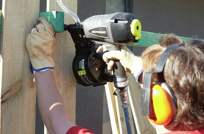 Person installing fence paling with nail gun.