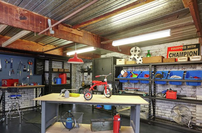 Organised garage with garage shelves full of assorted items and workbench in the middle of the room.