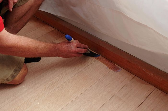 A person using a paintbrush to apply sealer around the edge of a hardwood floor