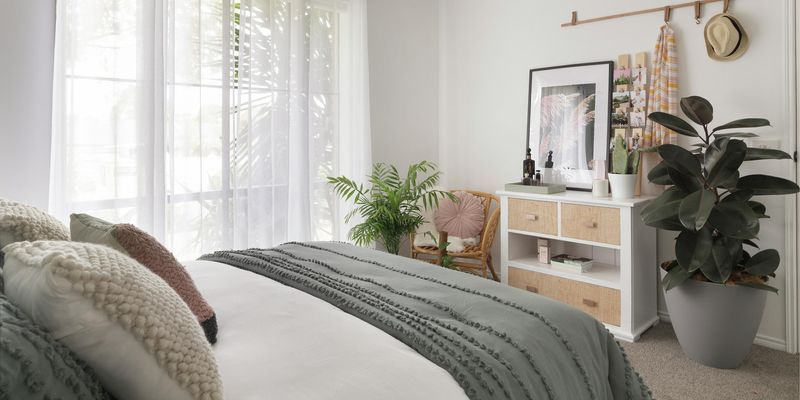 Bedroom with sheer curtains, bed, chest of drawers and potted plants.