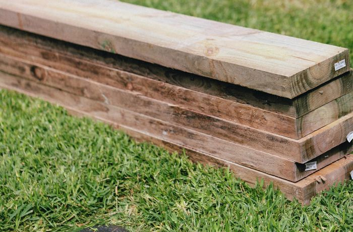 Wooden sleepers in a pile on grass