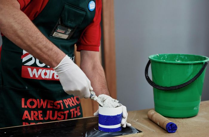 Close up of a Bunnings team member filling a small container with cement