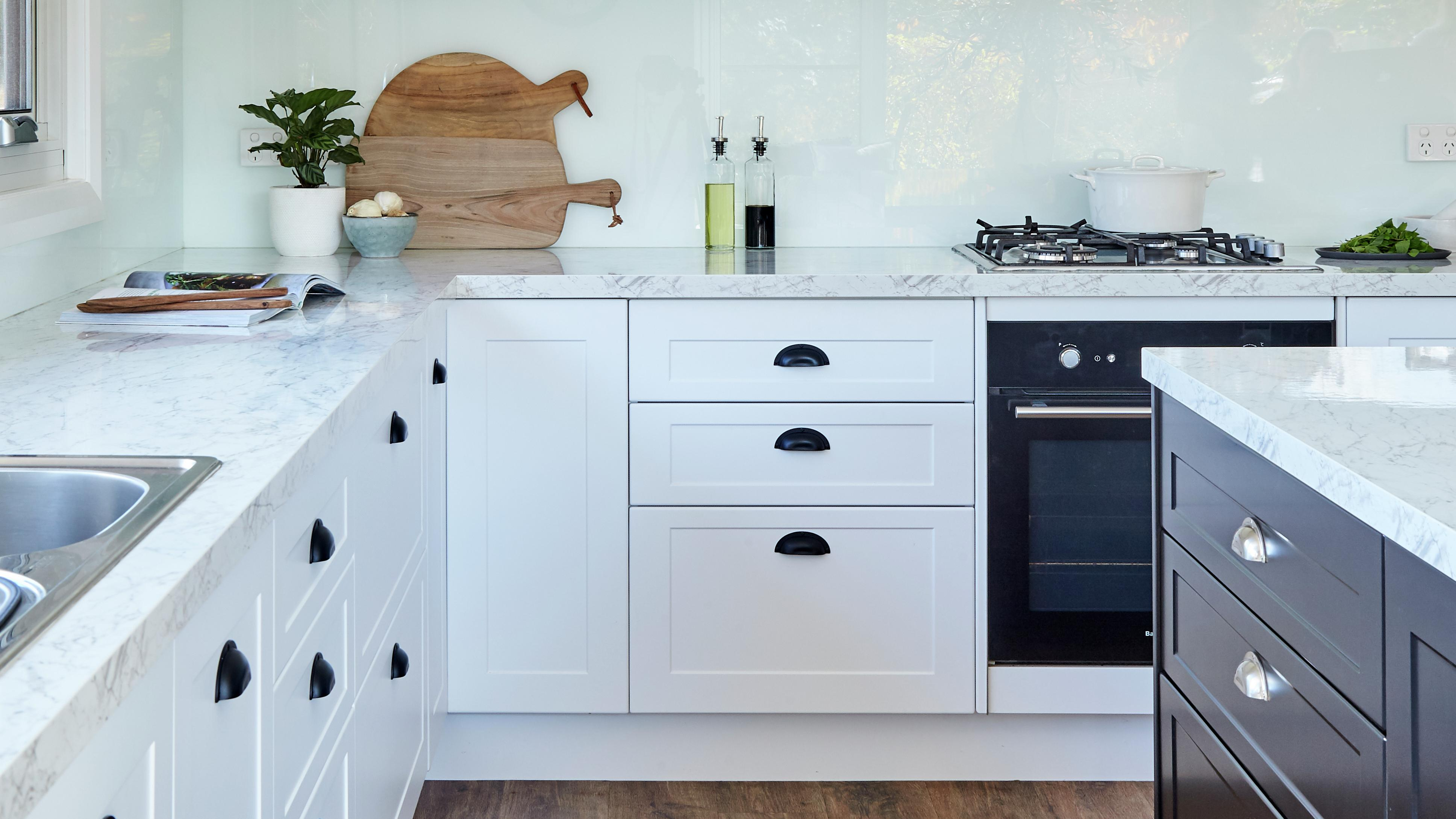 Kitchen featuring marble benchtops, white cabinetry with black handles and timber floorboards.