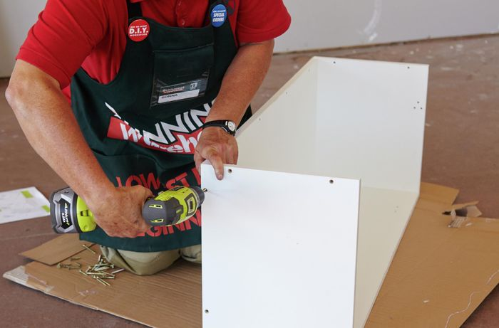 Person drilling cabinet sides to the base