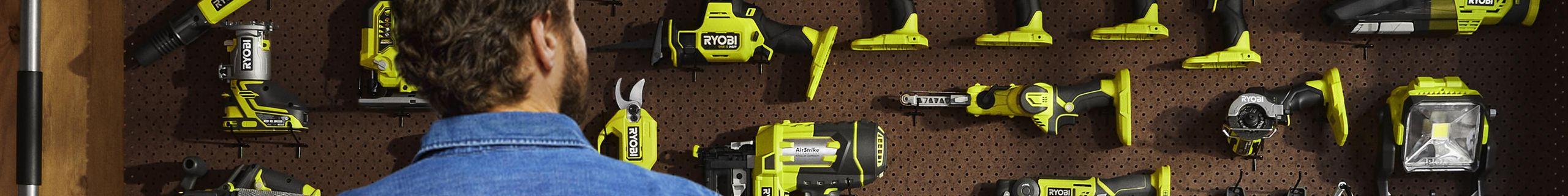Man looking at wall full of Ryobi power tools.