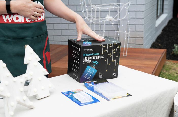A person standing at a table with a box of LED string lights and packets of fittings