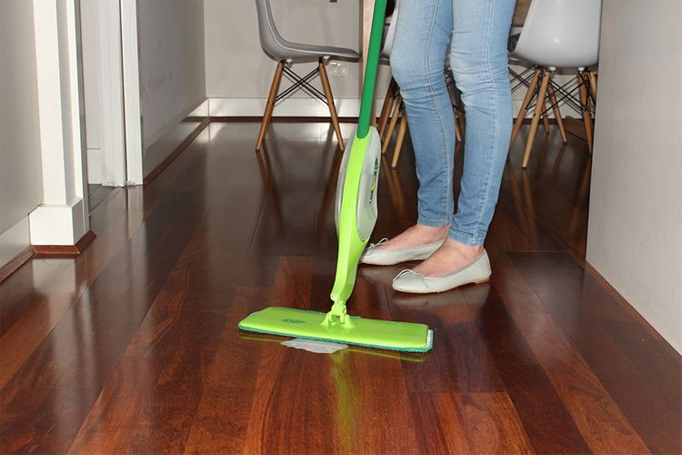 Person mopping a timber floor using a spray mop