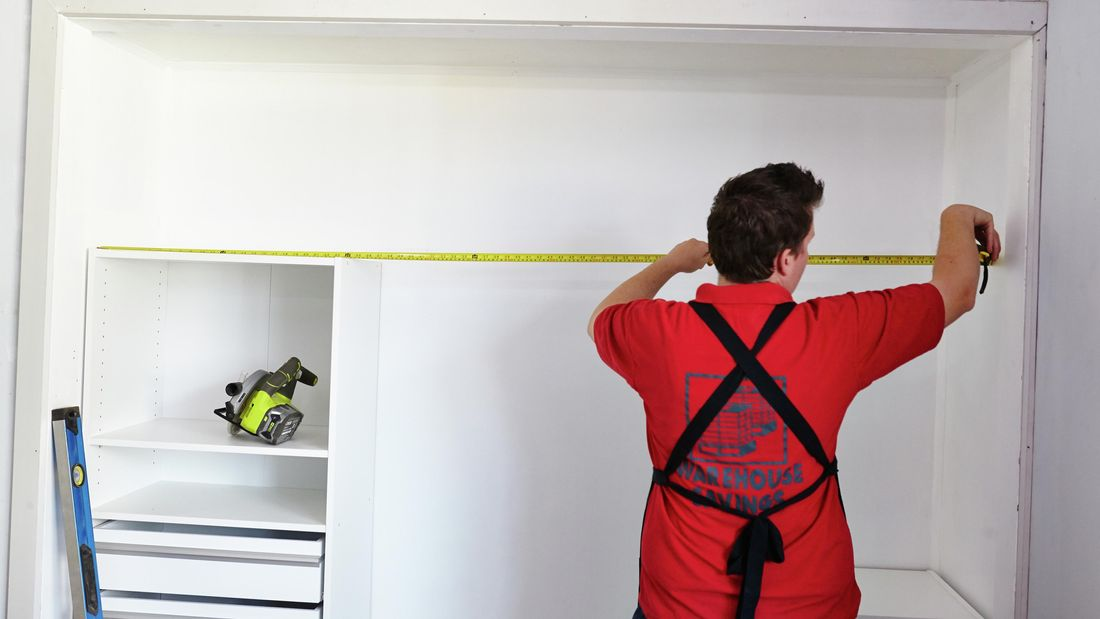 Person using measuring tape to measure inside of wardrobe.