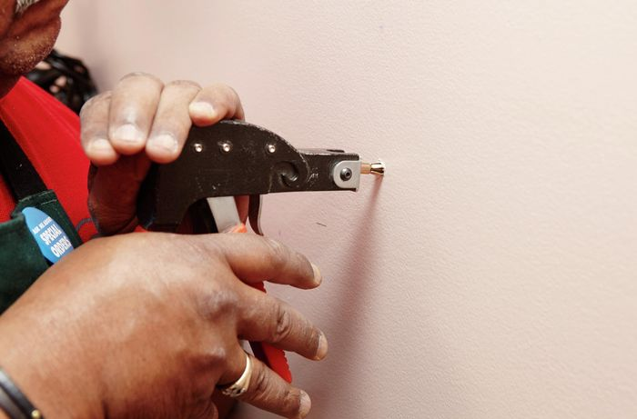 A person inserting anchors into a plaster wall using a wall anchor gun
