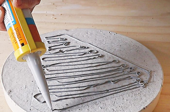 Person applying glue to base of grey concrete paver