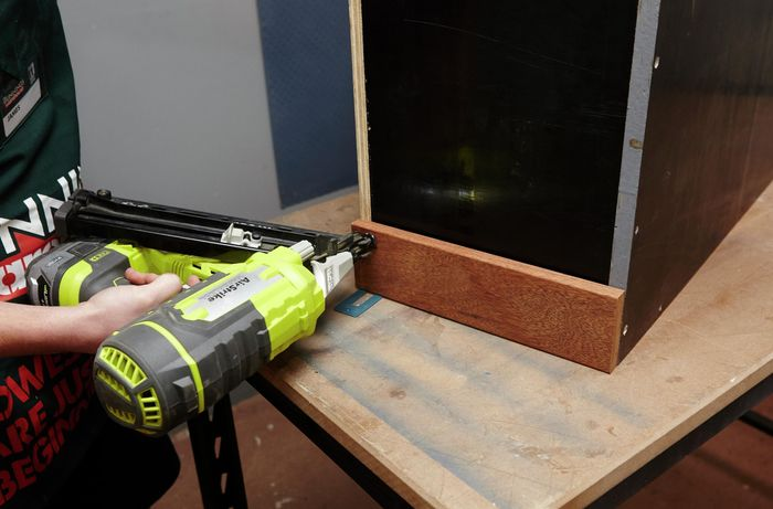 A person attaching a length of decking timber to a box using a nail gun