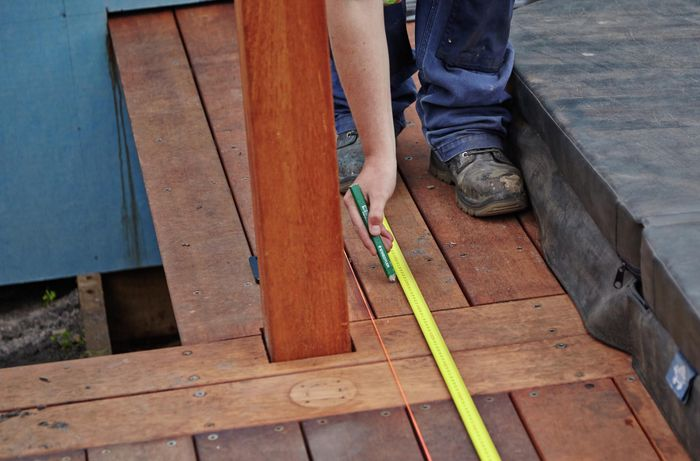 Person measuring timber deck.