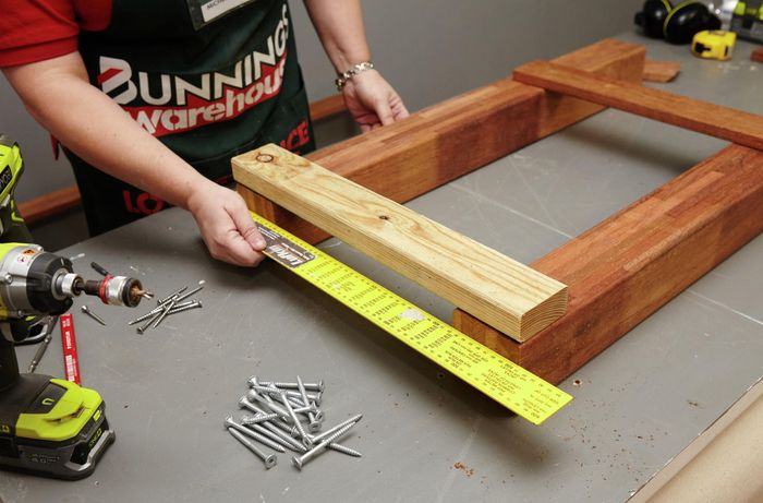 Person measuring wooden table legs with measuring tape.