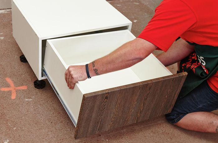 Person putting drawer into cabinet