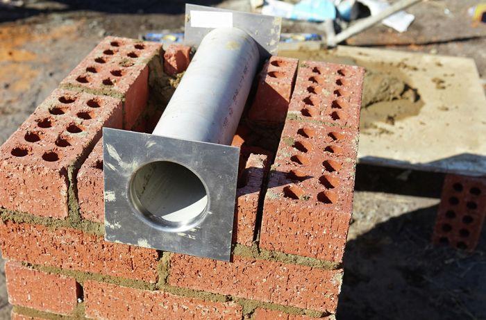 Pipe lying on top of bricks.