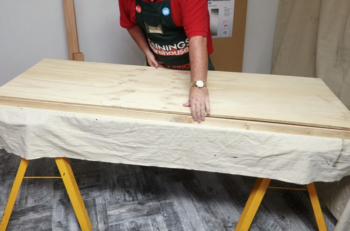 A person positioning a plywood sheet onto a timber frame
