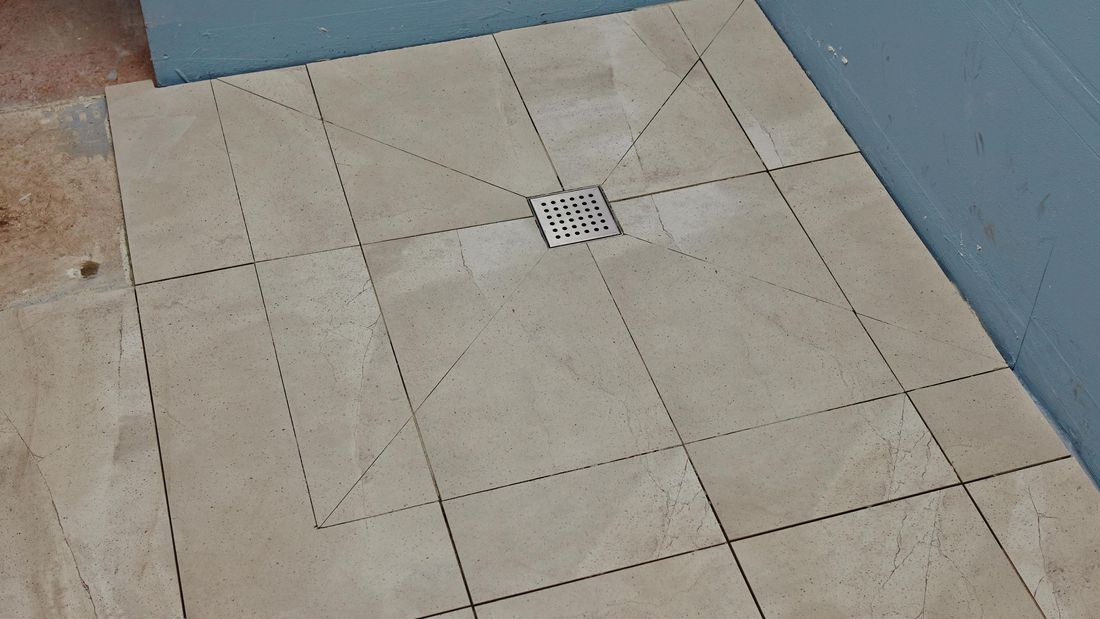 A tiled shower base with tiles cut on diagonals towards the drain hole