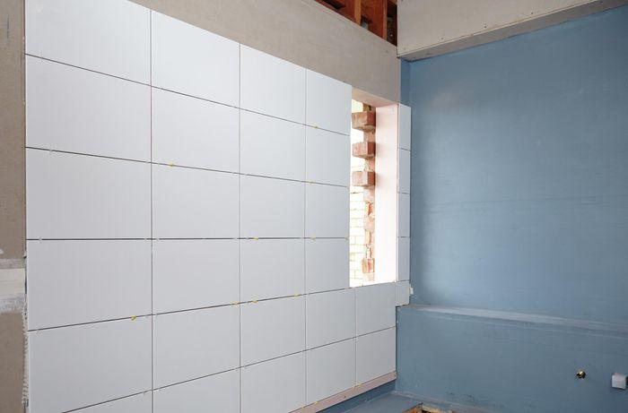 Freshly laid white tiles on bathroom wall.