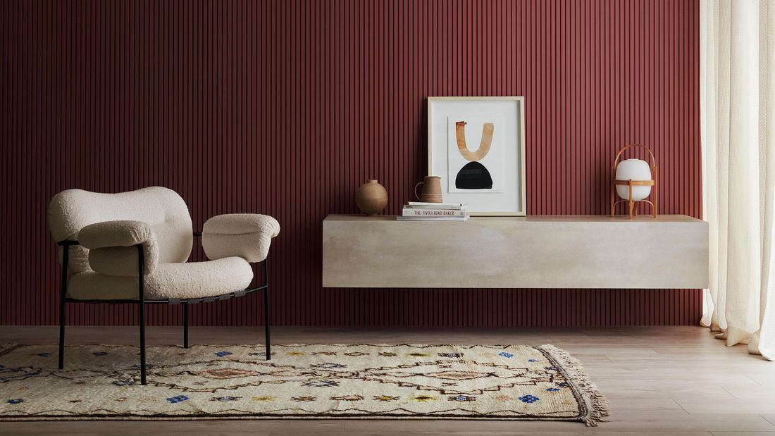 Living space with occasional chair, rug, concrete look floating shelf with accessories. Batten 25design.