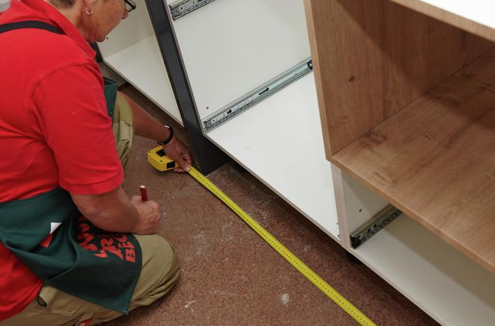 A person kneeling on the floor measuring the length of a cabinet