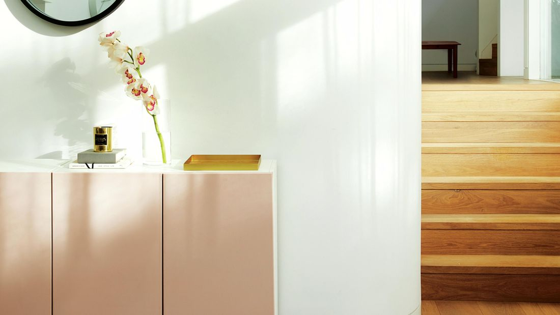 White buffet unit with dusty pink doors against a white wall