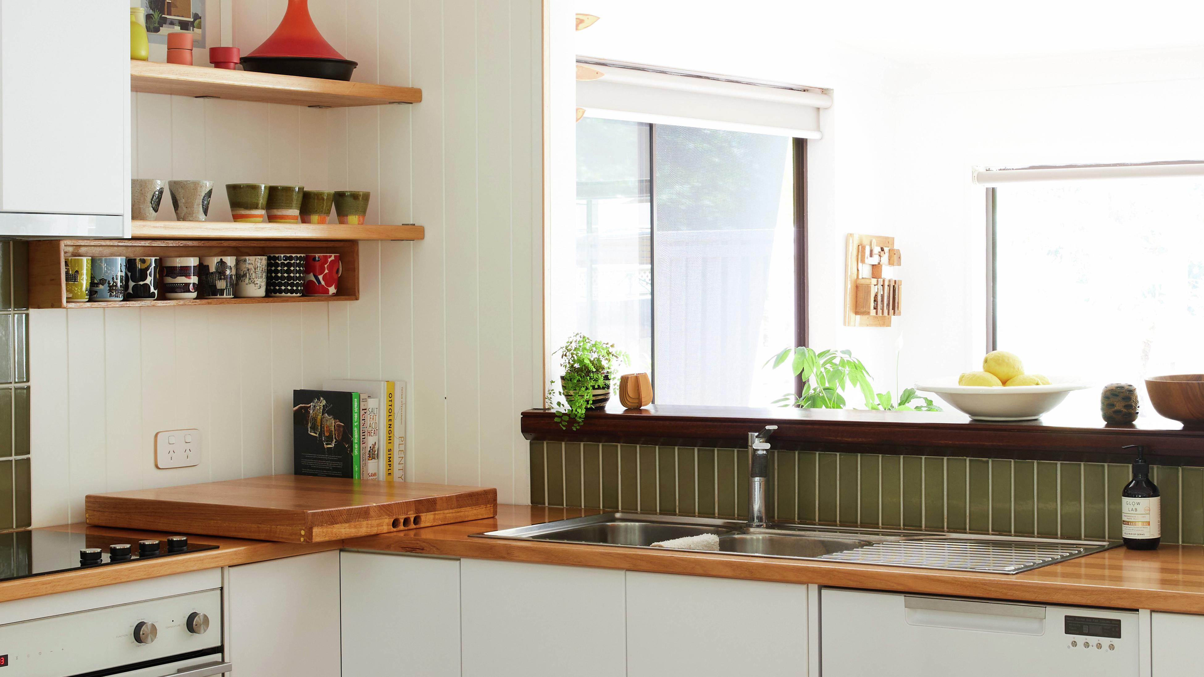 Modern and warm kitchen with timber benchtops and green tiles