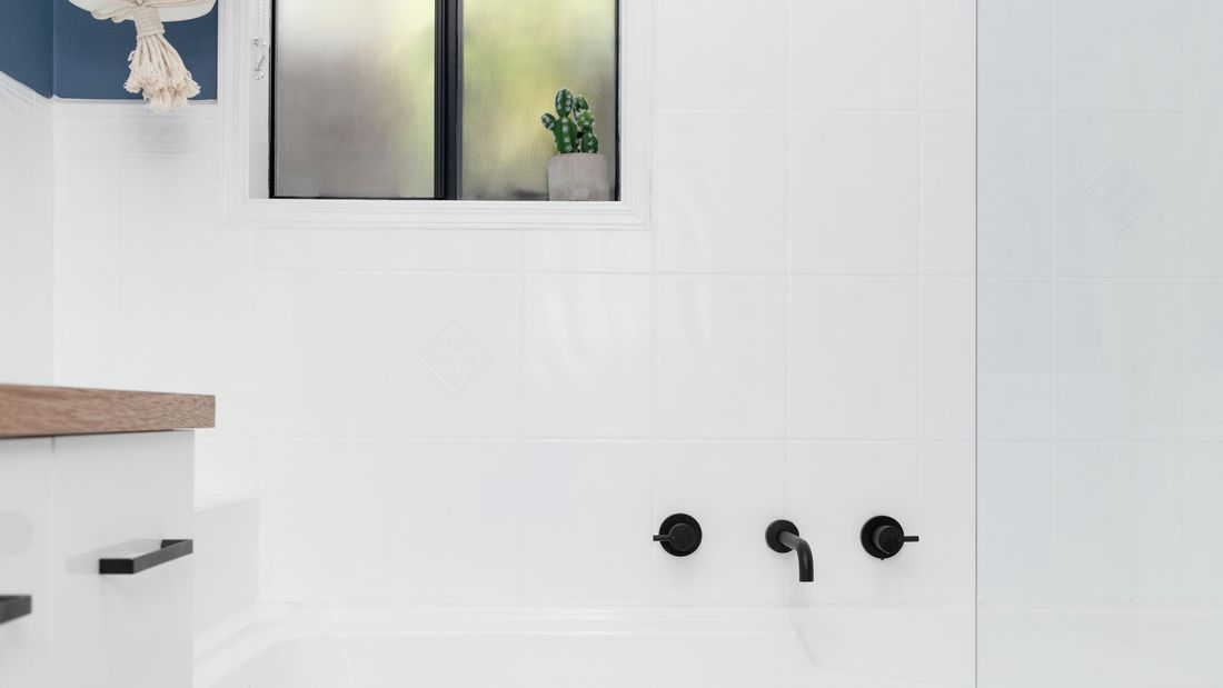 Wide shot of an in-built bath in a white-tiled bathroom