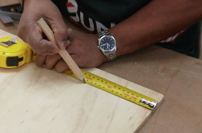 Person measuring and marking ply panel with tape measure and pencil