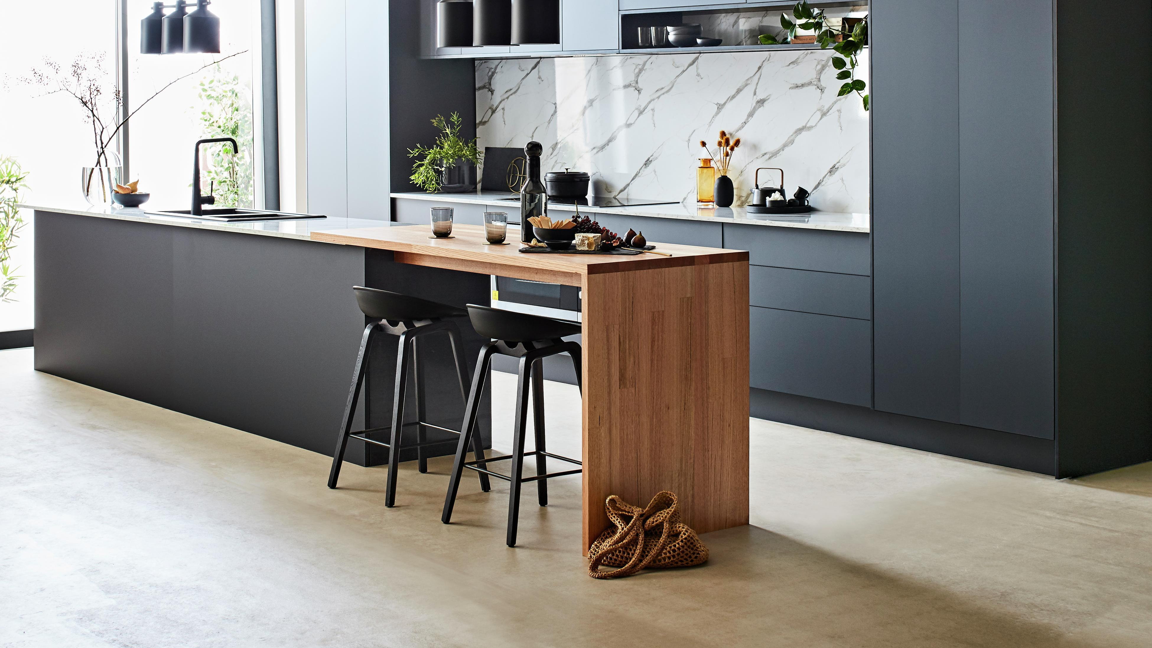 Kitchen featuring timber island, black cabinetry and marble splashback.