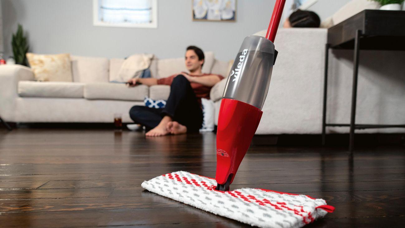 A person using a Vileda microfibre spray mop to clean timber flooring