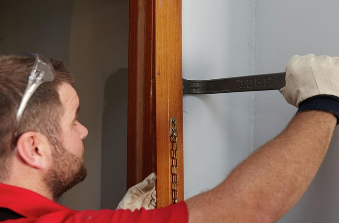 A door jamb being pried free from the wall with a pry bar