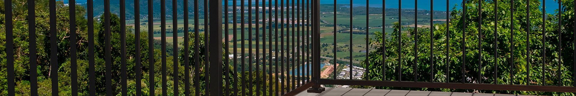 Balcony with view of town below and black balustrade fence.