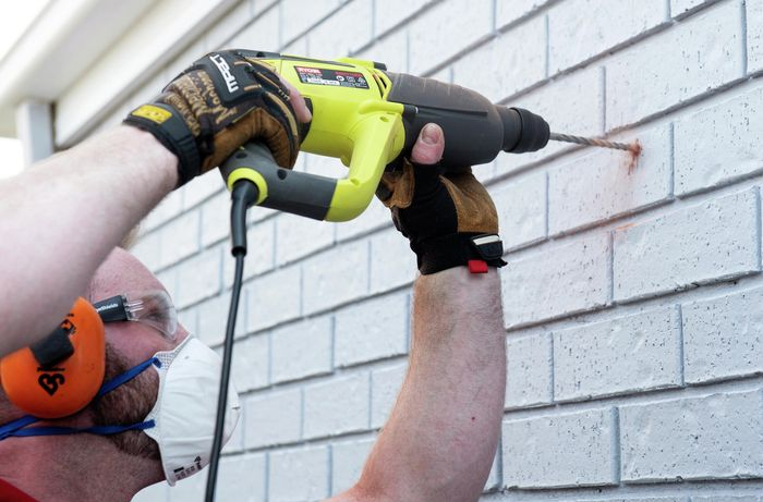 Person drilling hole into brick wall