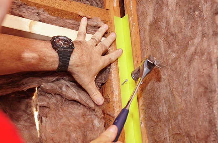 Internal angles being nailed into place on a bare wall
