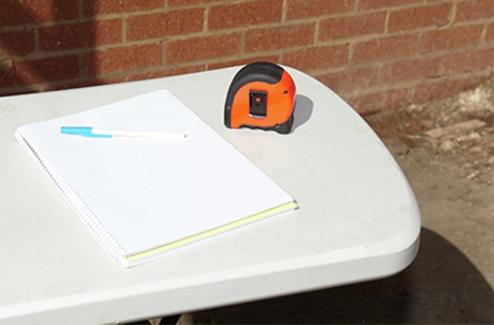 A pad and measuring tape on a table outside
