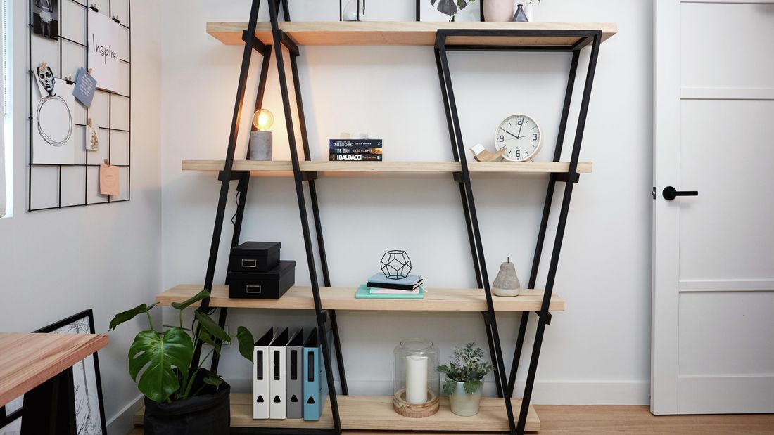 DIY industrial wooden bookshelf with various decorated items on it.