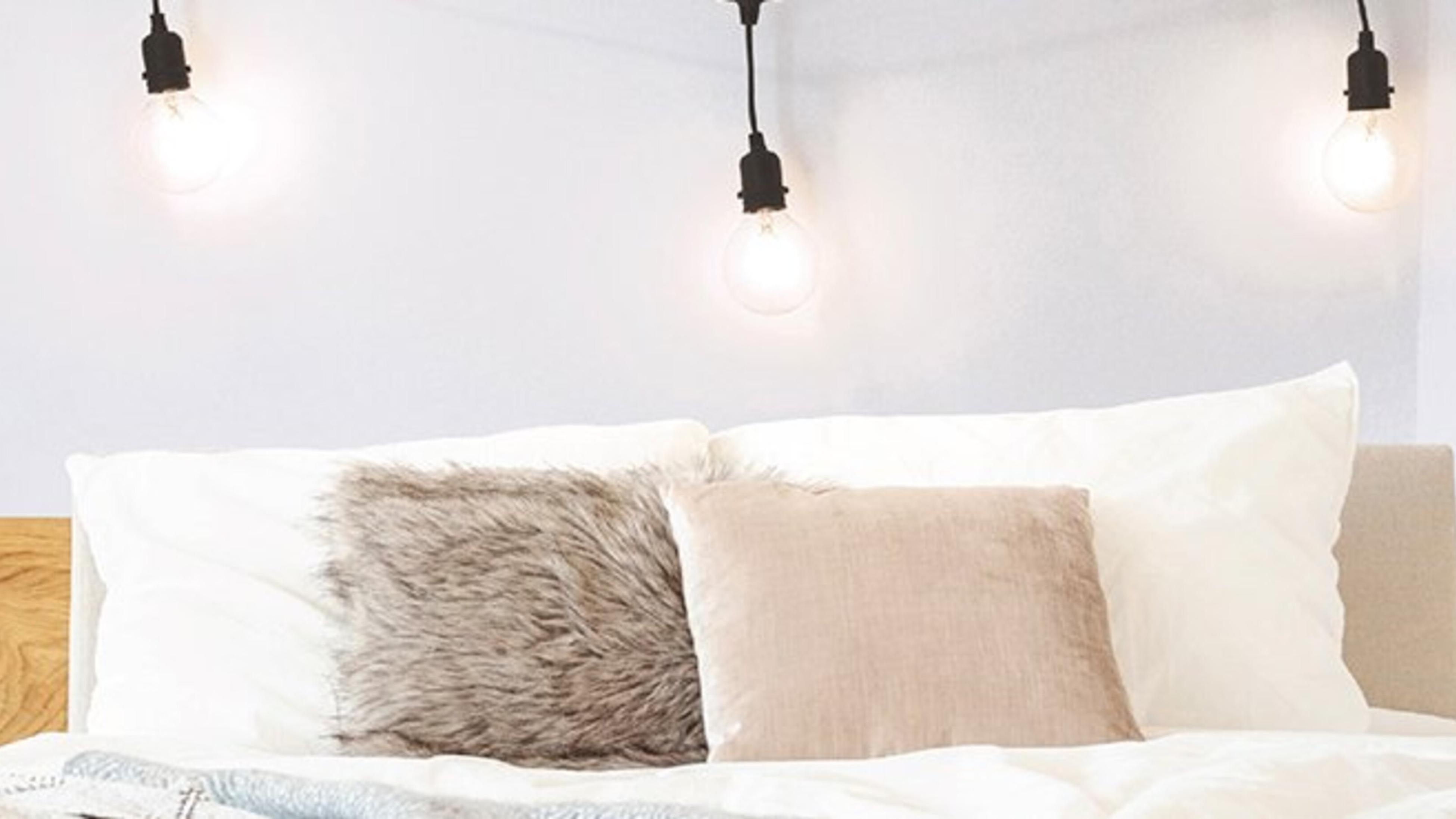 A bed with cushions on it and a string of light bulbs hanging above it.