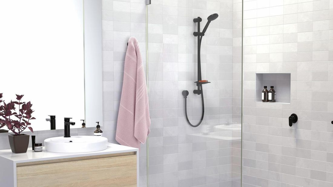 Bathroom with grey tiles, black tapware and pink towel hanging up.