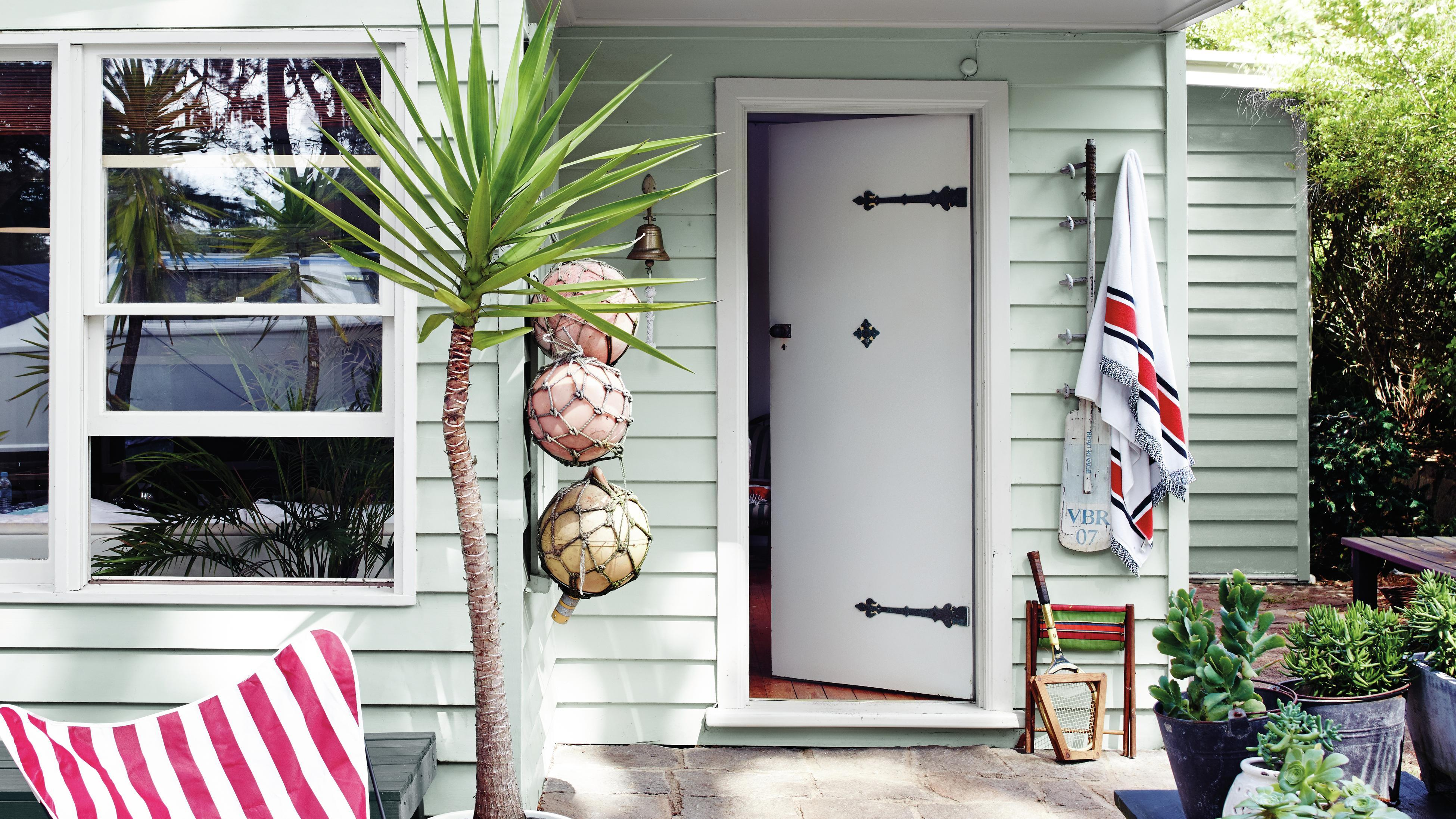 Outside of a weatherboard home with various plants and decor displayed.