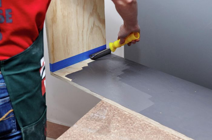 A person painting the inside face of a timber shelving unit using a mini roller