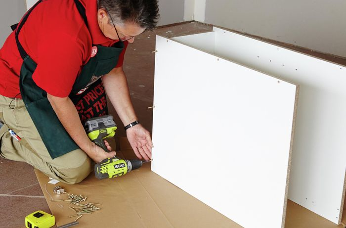 Person attaching base panel of cabinet