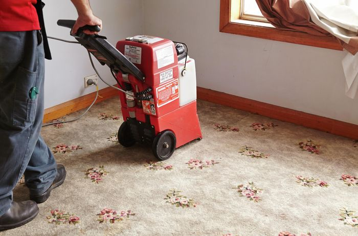 An industrial vacuum being used to clean a carpet