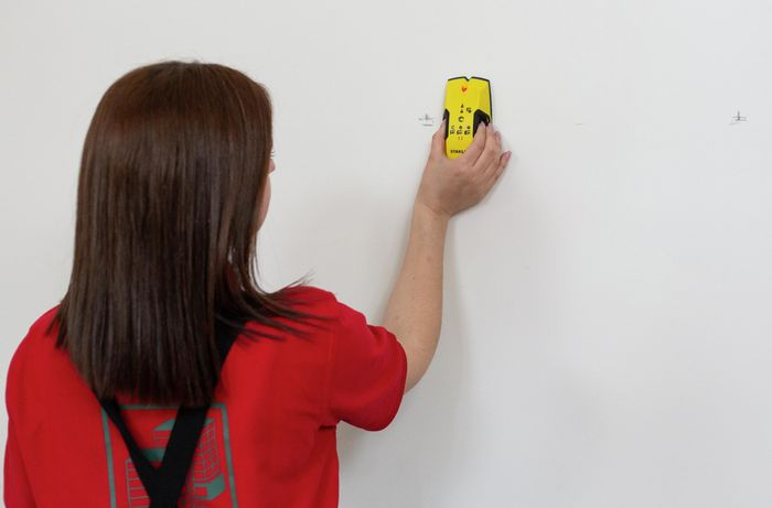 Person using a stud finder on a plaster wall
