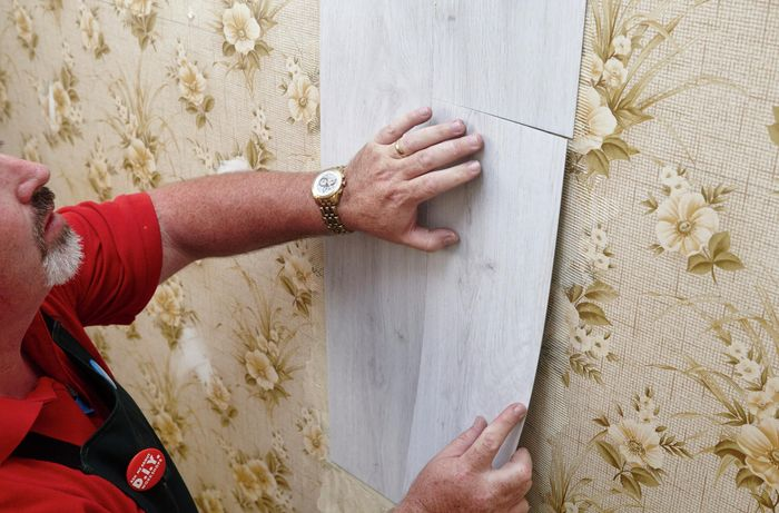 Faux wooden panels being applied over a wallpapered wall